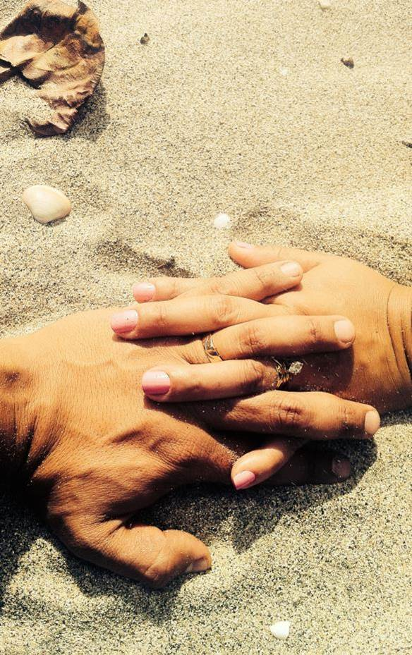 Married couple holding hands on the sand