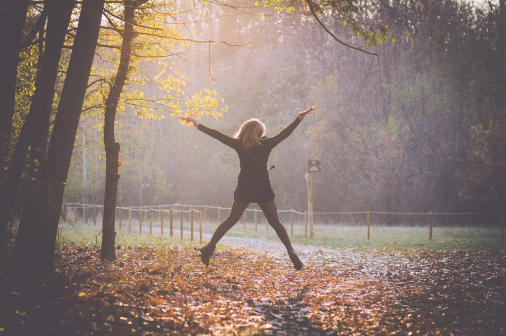 Woman jumping for joy in the woods.