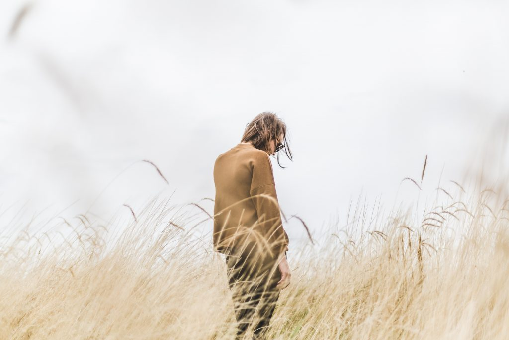 Woman feeling alone in a sea of grass.
