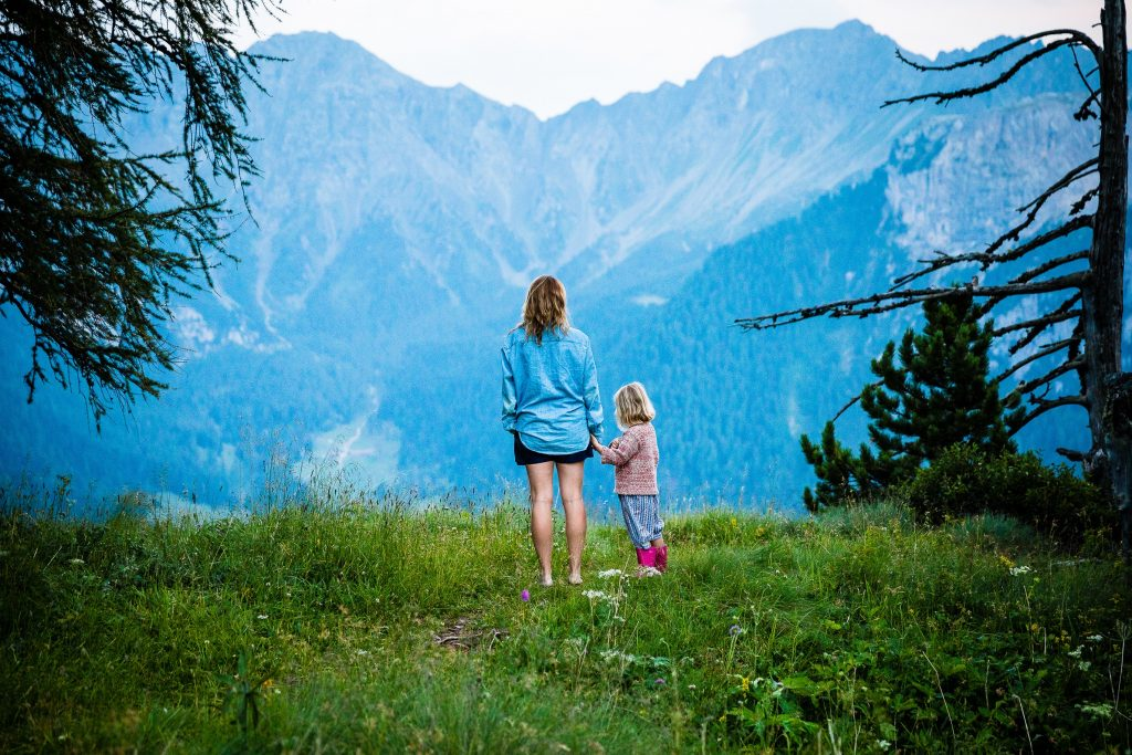mother with daughter in nature looking at a mountain