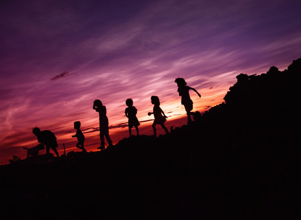 silhouette six children with dog playing