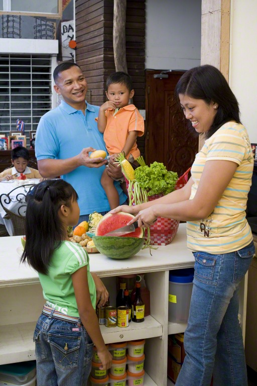 Mother slicing watermelon with father and children watching