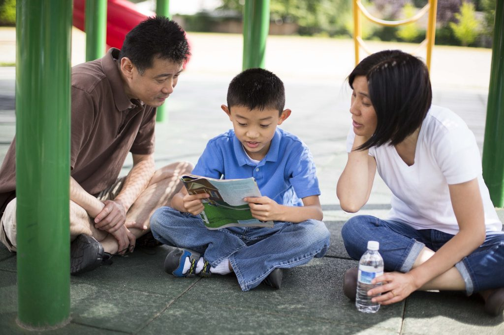 father and mother reading with child at the playground