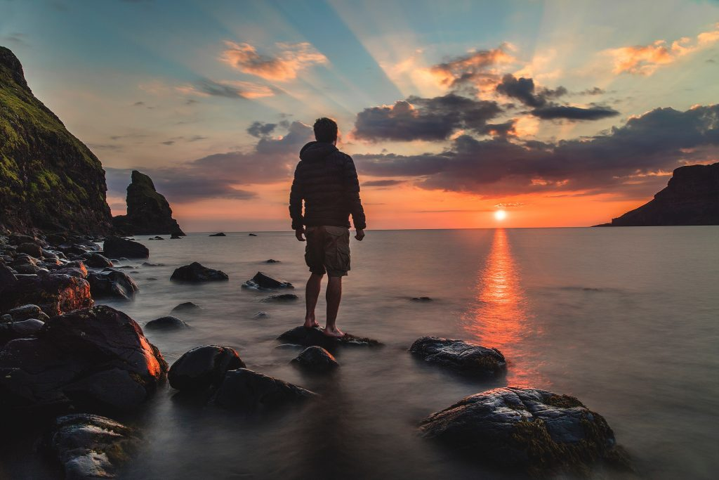 man standing facing the sunrise